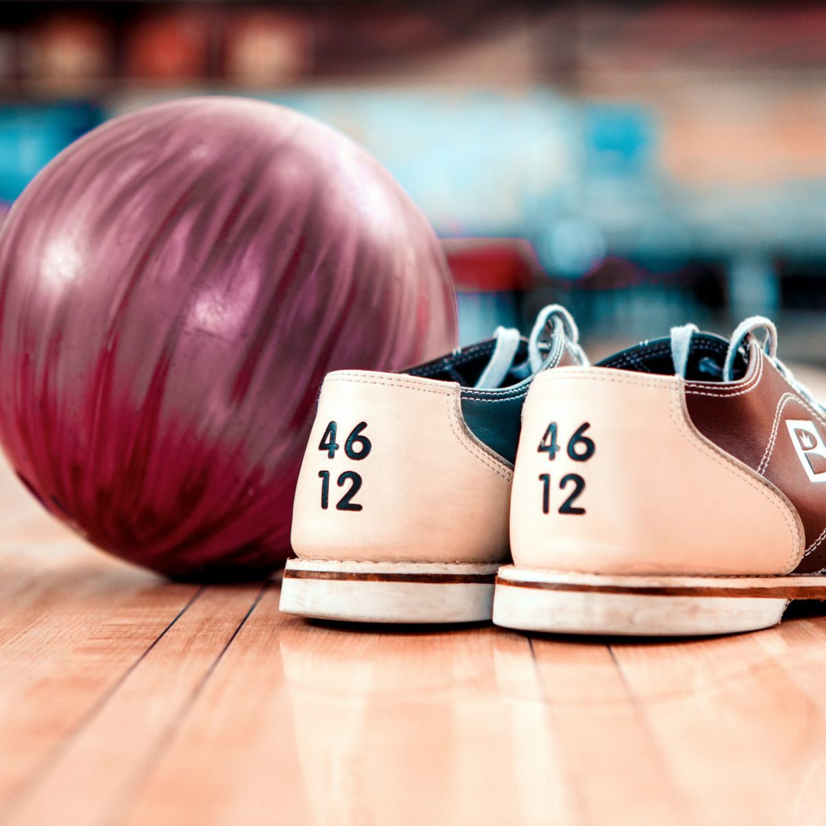 Bowling equipment. Close up of bowling shoes and lilac ball lying on bowling alley